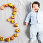 A young baby with the number three spelled out in apples