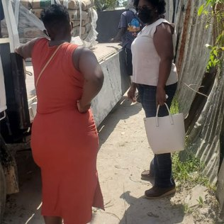 Former Minister of Government and founder of the Broomes Foundation, Simona Broomes in discussion with one of the fire victims Jeanelle Clarke-December