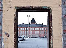 Kuva vanhasta rakennuksesta kurkistusikkunasta katsottuna