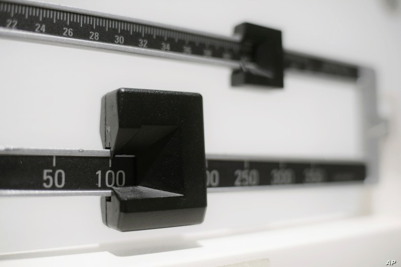 This Tuesday, April 3, 2018 photo shows a closeup of a beam scale in New York. New research released on Wednesday, April 4, 2018 suggests there's a critical window for overweight kids to get to a healthy level. Those who shed their extra pounds by…