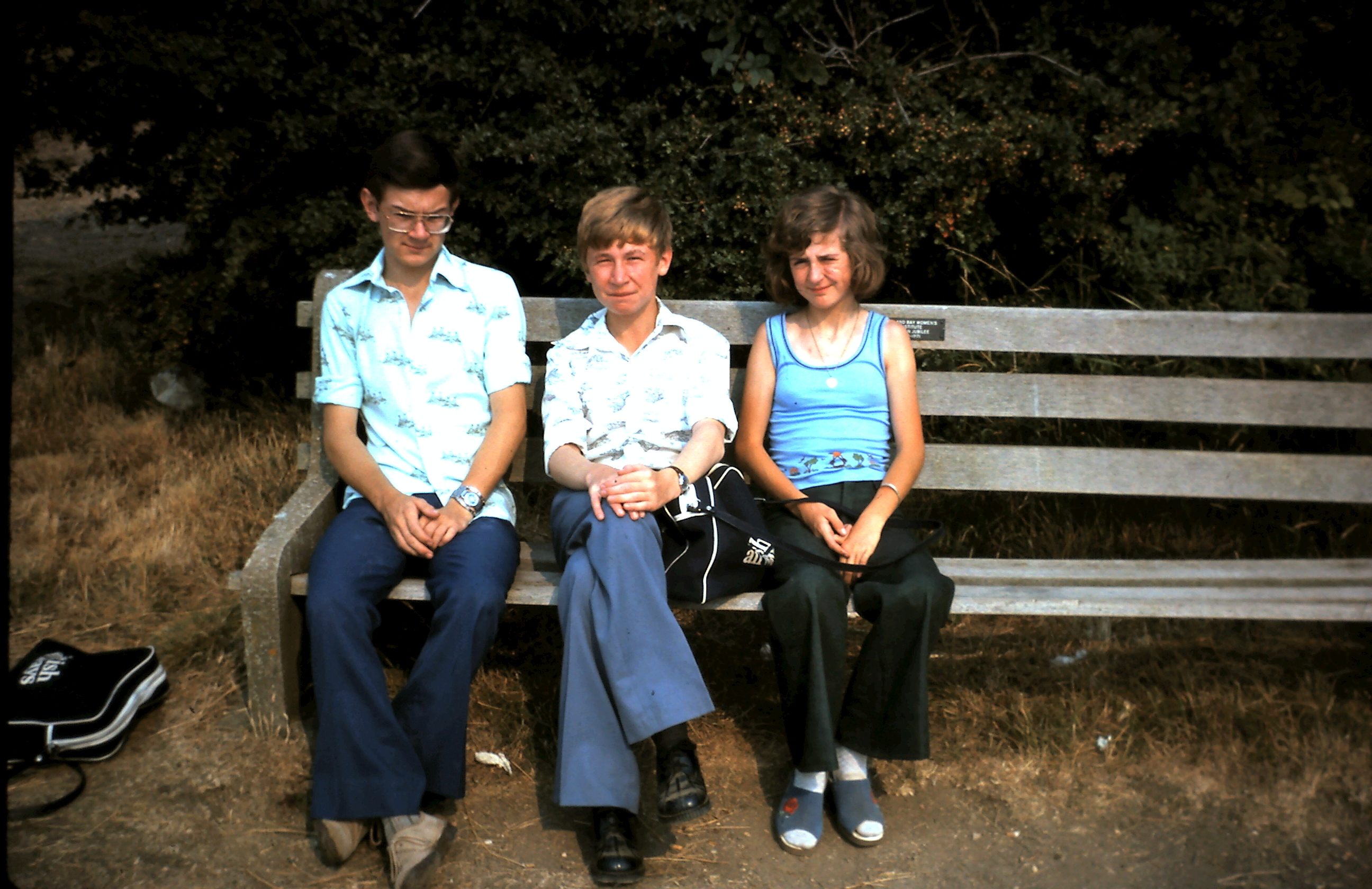 The author sits on a bench with brother Mark to his right and his sister Dawn on his right.  The clothing is very seventies, with all wearing bell bottomed, flared trousers.  The author sits awkwardly with crossed legs and his hands clasped around his knees, rather camply