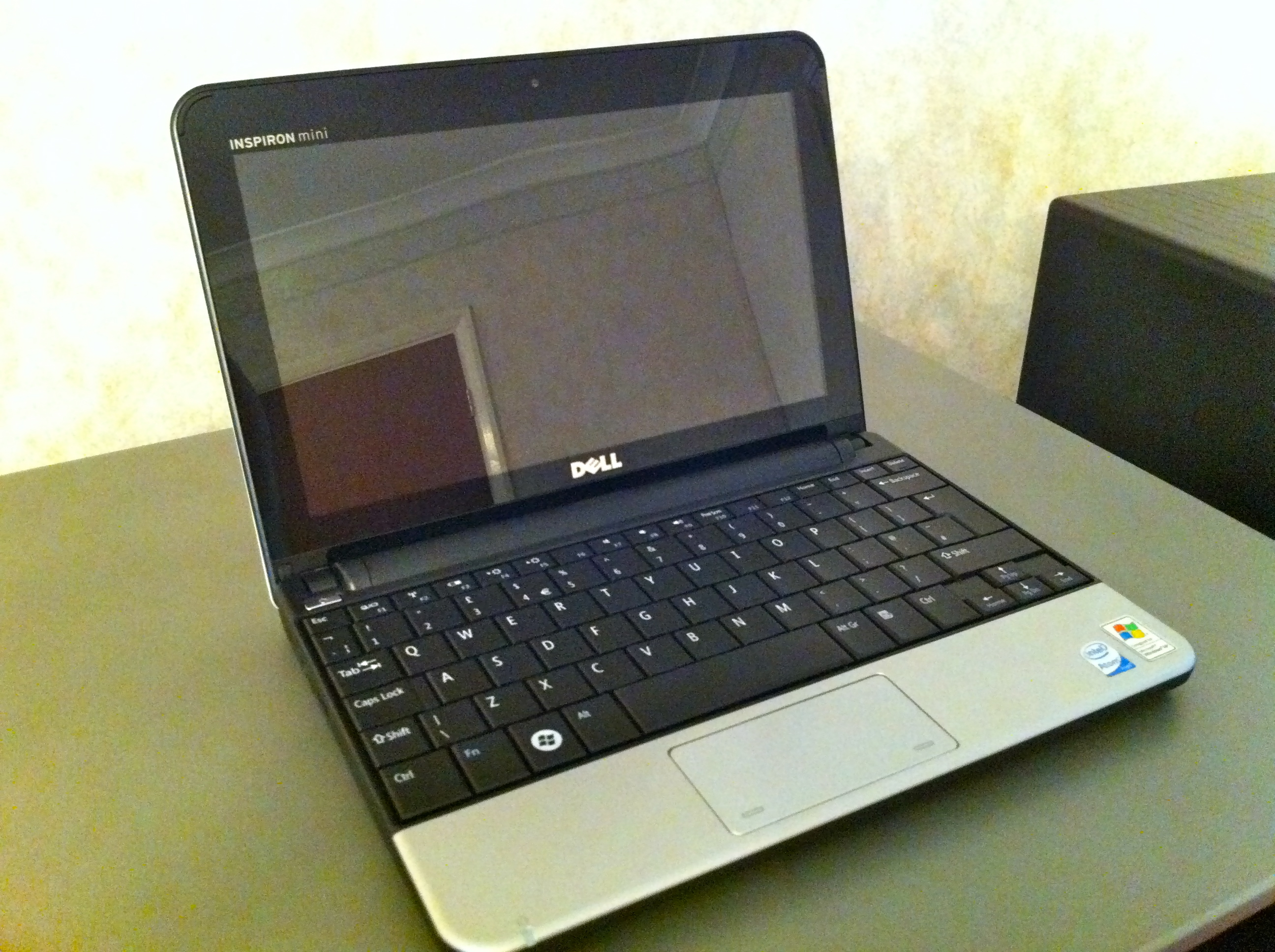 An opened but switched off Dell Inspiron Mini 10 Notebook.  It has a glossy screen, black bezel and keyboard and a silver trackpad and wrist rest area