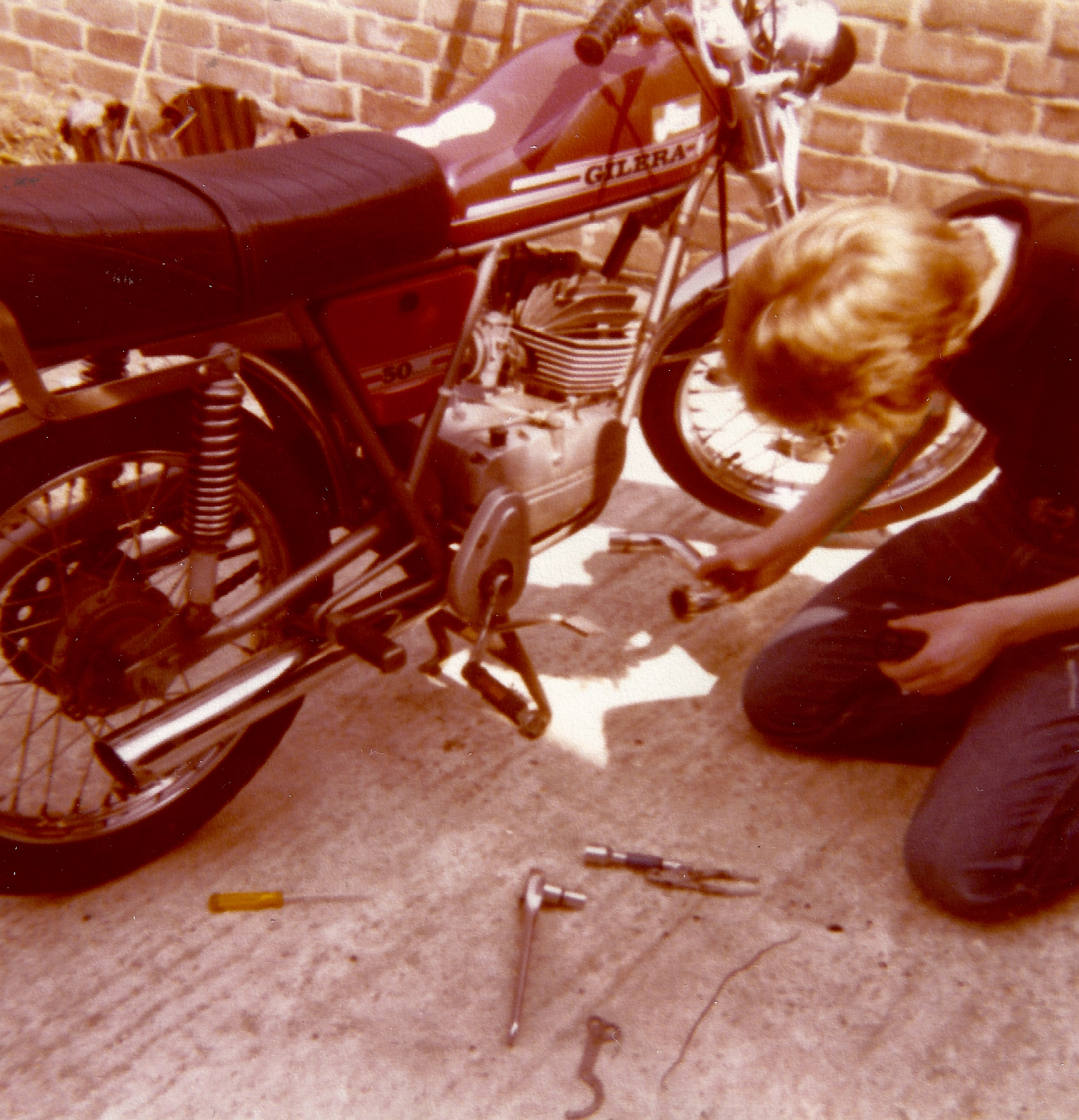 Vince on his knees fixing a removed exhaust pipe from the Gilera moped