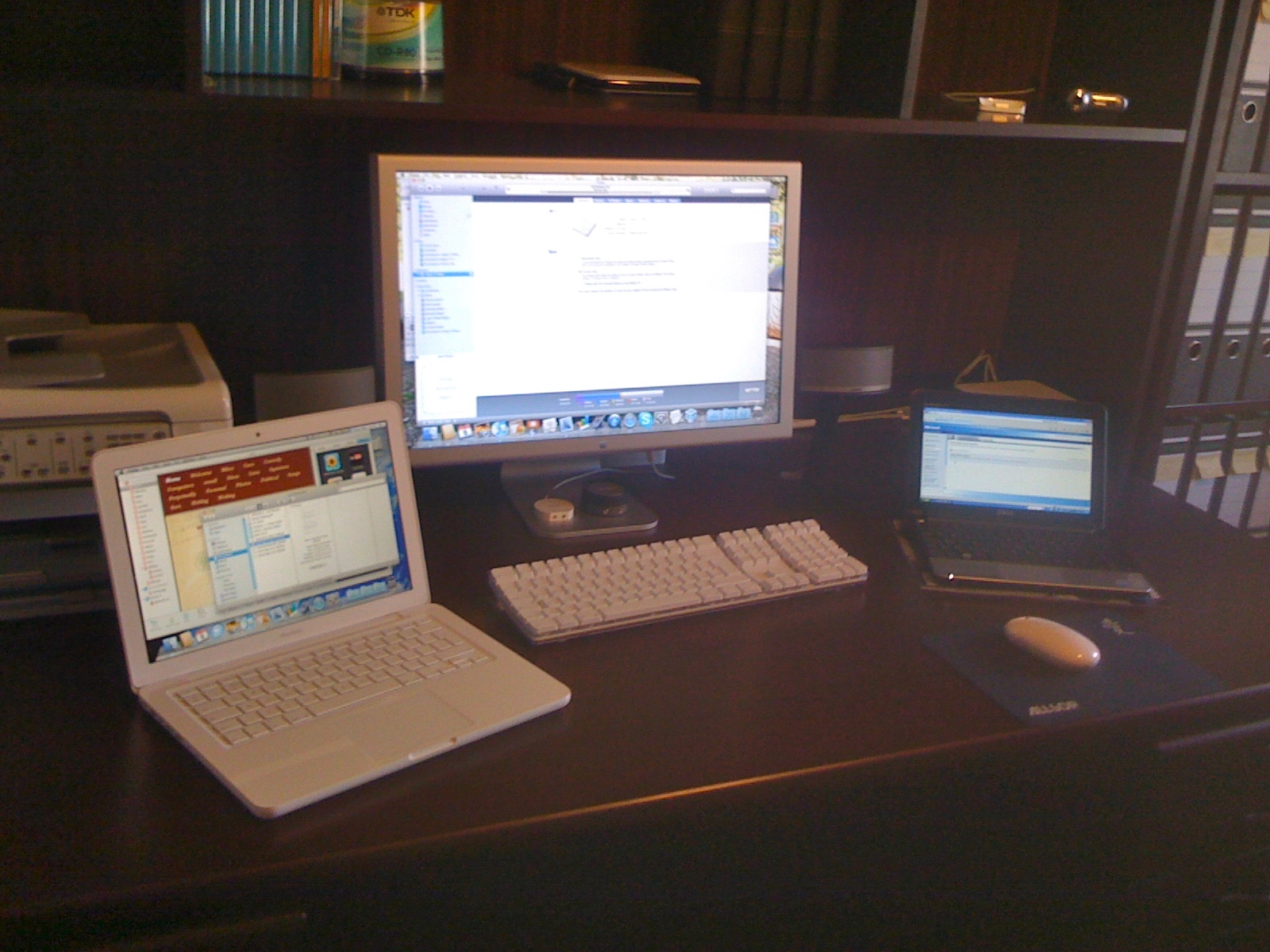 A white MacBook sits to the left of the Apple Cinema Display and on the right is a Dell Notebook