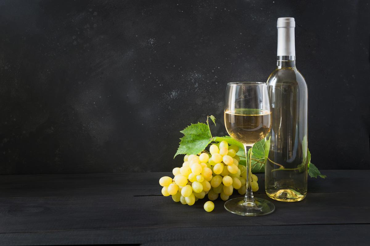 vino bianco in bottiglia, calice e grappolo d'uva bianca
