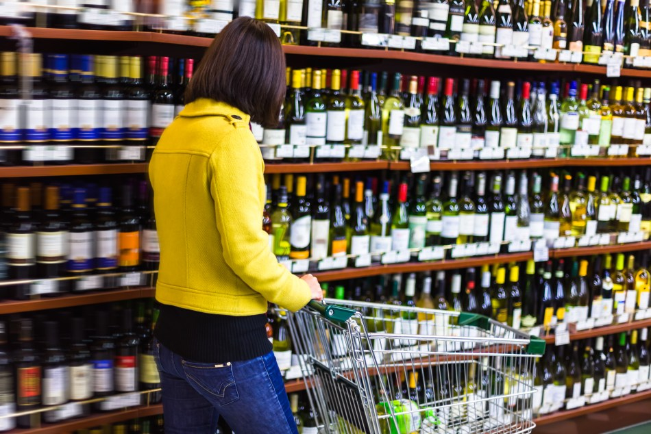 Young woman shopping in the supermarket wine shelves (pic: iStock)