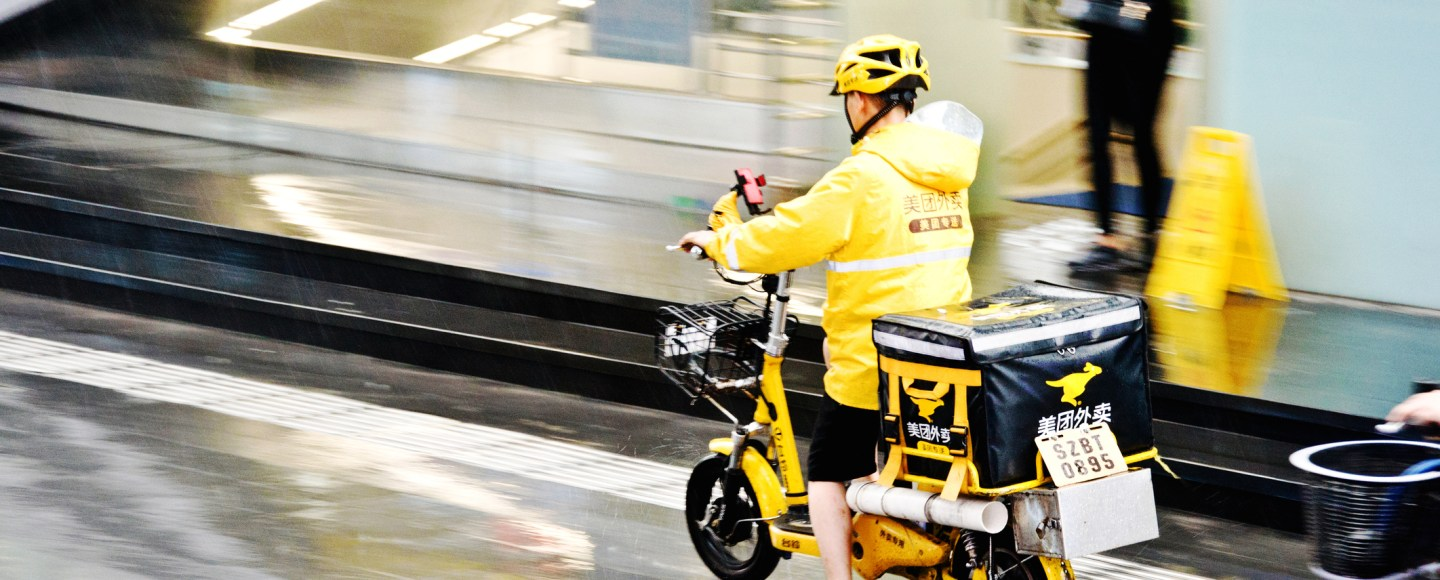 A Meituan food delivery worker on motorcycle in the rain in Futian Central Business District, Shenzhen - China. Meituan, founded in 2010 by Wang Xing, is an app that users in China turn to for food delivery, restaurant deals, movie tickets, hotel and travel bookings, and more. (pic: iStock)