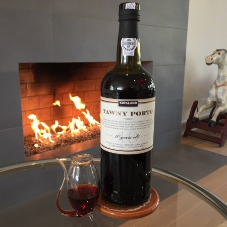Bottle and glass of Kirkland Signature Tawny Port in front of a fireplace.