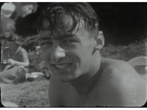 A still shot showing a from a vintage home movie of a beach party in the 1950s