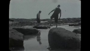 A Still image from a black & white film by a rocky seafront