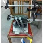 geleimter Stuhl mit Spanngurten, Schraubzwingen und einem Gewicht