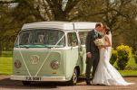 kissing by wedding campervan