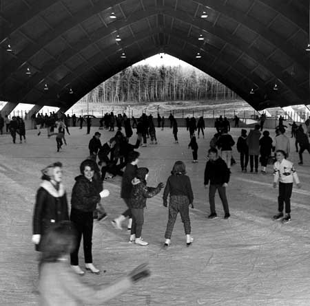 Students and area children skate in the newly opened UConn Ice Rink in 1965. The rink was home to the ice hockey team. Only a boat-shaped roof protected skaters from the elements, and many fans (and former hockey team members) can remember blustery cold winds blowing through the structure. The old ice rink was demolished to make way for the Ice Arena that opened in 1998. [University Archives]