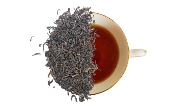 English breakfast tea leaves displayed over a brewed cup of tea