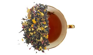 Black tea with ginger and turmeric pieces displayed over a brewed cup of ginger turmeric tea