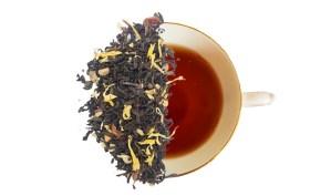 Loose leaf pumpkin spice tea displayed overtop of a brewed cup of tea