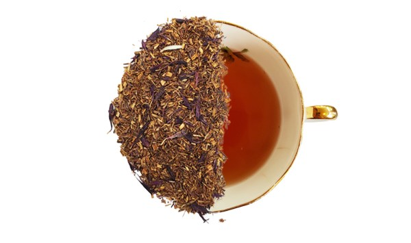 rooibos cream of earl grey tea leaves overtop of a cup of brewed tea to display the product