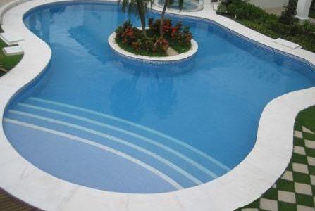 Construção de piscina com ilha ao centro.