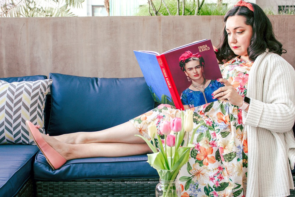 Bianca reading a book about Frida Kahlo outside