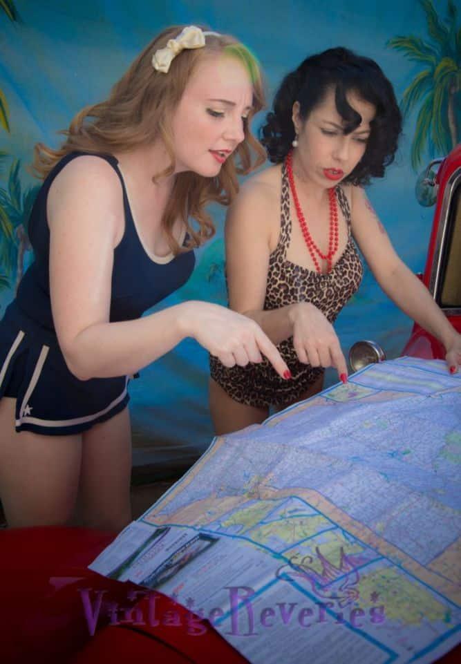 pinup models looking at a map