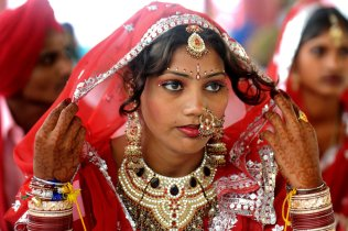 An Indian bride sits during a mass marri