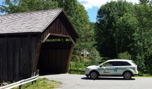 A WCVT service vehicle in rural Vermont about to cover a historic covered bridge.