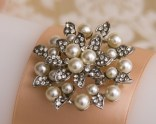 Large brooch with ivory pearls and rhinestones decorate unity candle set.