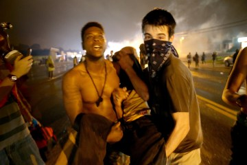 Image: A protester is carried after being overcome by tear gas