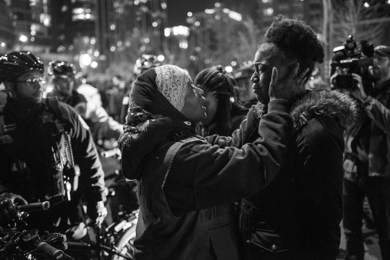 Community organizer and violence interrupter Ameena Matthews comforts protestor Kirah Moe during a particularly emotional moment while protesting against police brutality in Chicago. Upwards of 500 hundred people marched throughout downtown Chicago on Tuesday, November 24 to protest the police killing of Laquan McDonald at the hands of Chicago police officer Jason Van Dyke. McDonald was shot sixteen times and the video was withheld from public view until a judge ordred it released. McDonald was holding a small knife but was shot repeatedly in the dashcam video. The family was paid 5 million dollars in a settlement with the City of Chicago, but yesterday officer Van Dyke was also charged with murder after a whistleblower brought the video to the attention of a local journalist who then sued the city to have it released. The City of Chicago's Police Department has a long and difficult history associated with police brutality reaching back decades.