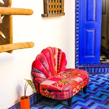 Gorgeous fabric chair that works in a corridor and nicely contrasts with blue tiled floor. http://salutmaroc.com