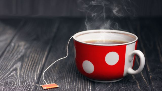 a red tea cup with white polka dots on a grey background