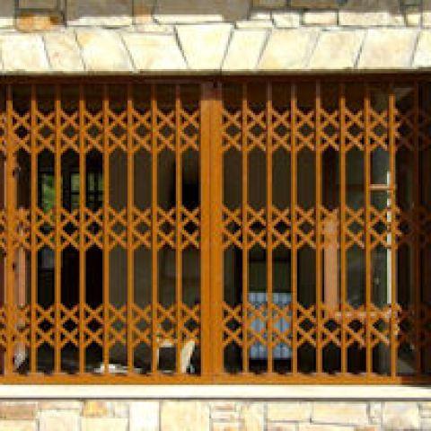 Rejas de seguridad plegables con láminas dobles de acero de Viometaloumin en una casa de piedra.