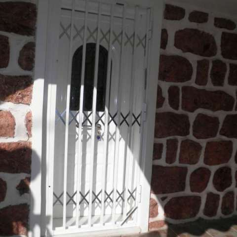 Retractable security gate for a door to a holiday home