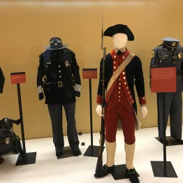 Another segment of the exhibit's showcase, with uniforms from 1778 - present shown
