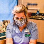 masked vet tech during exam