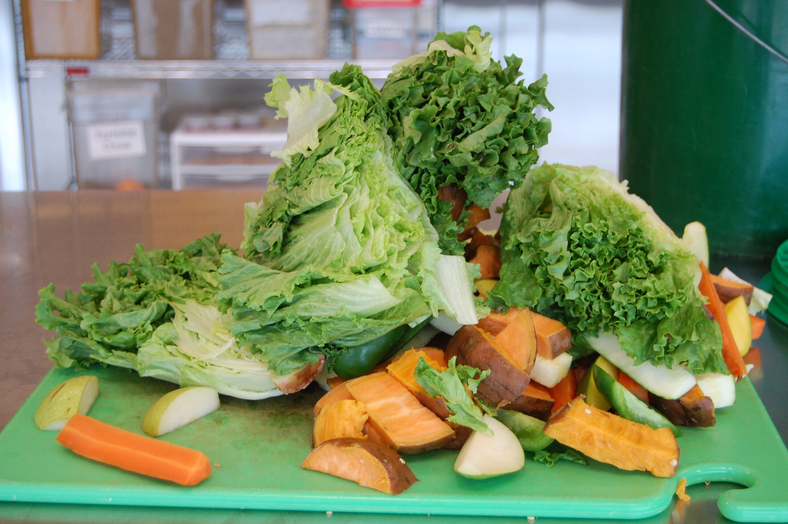 pile of chopped lettuce, carrots, apples, sweet potato, peppers on green cutting board