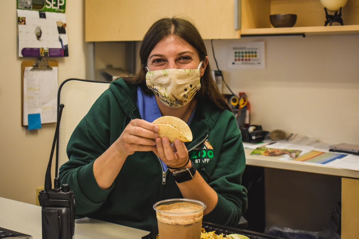 woman in mask holds taco