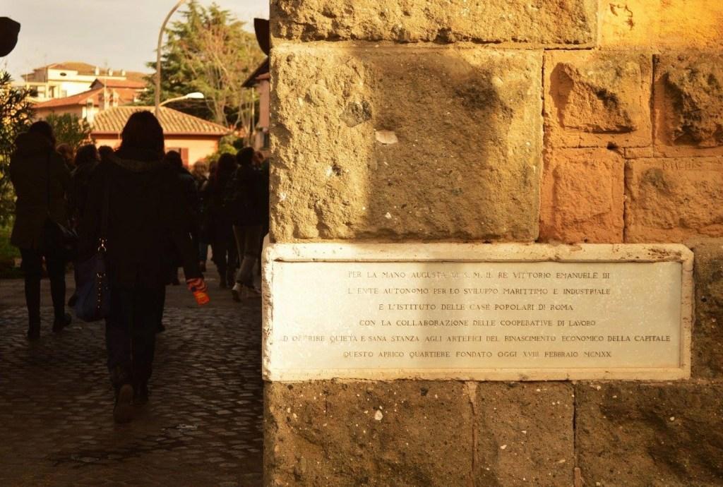 La lastra di marmo posta sotto l'arcata che dal palazzo di Piazza Brin determina l'accesso al nucleo originario della Garbatella. L'iscrizione riporta la data di fondazione, il 18 febbraio del 1920 (photo credits Roma Slow Tour)