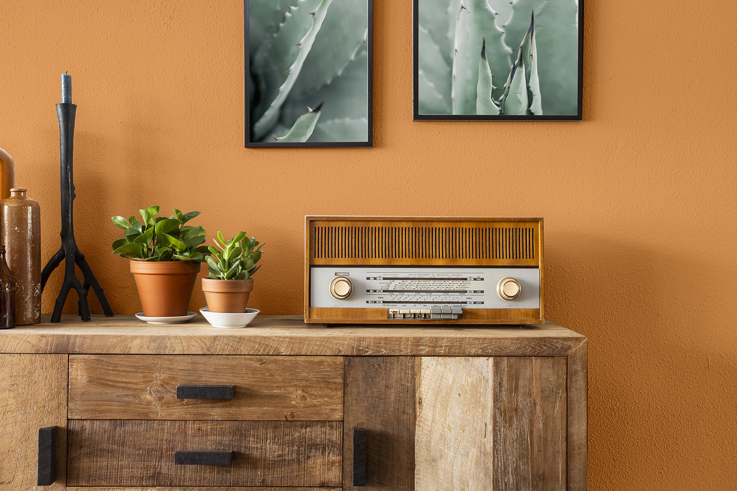 Retro living room design with cabinet and radio along with green plants and blank paintings, white wall