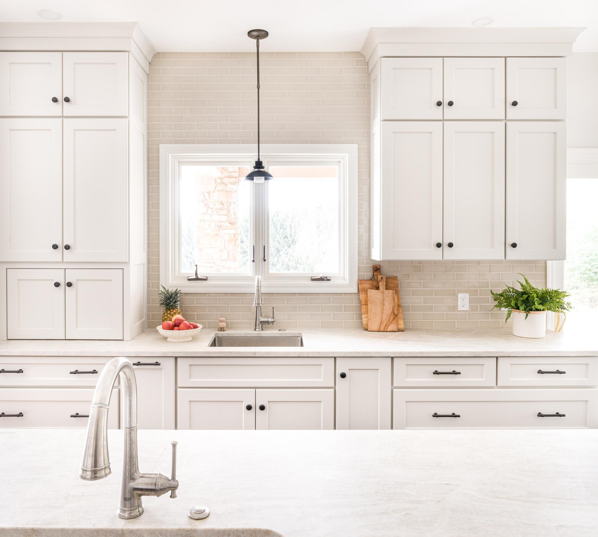 White cabinets and kitchen counters with cutting boards and plants