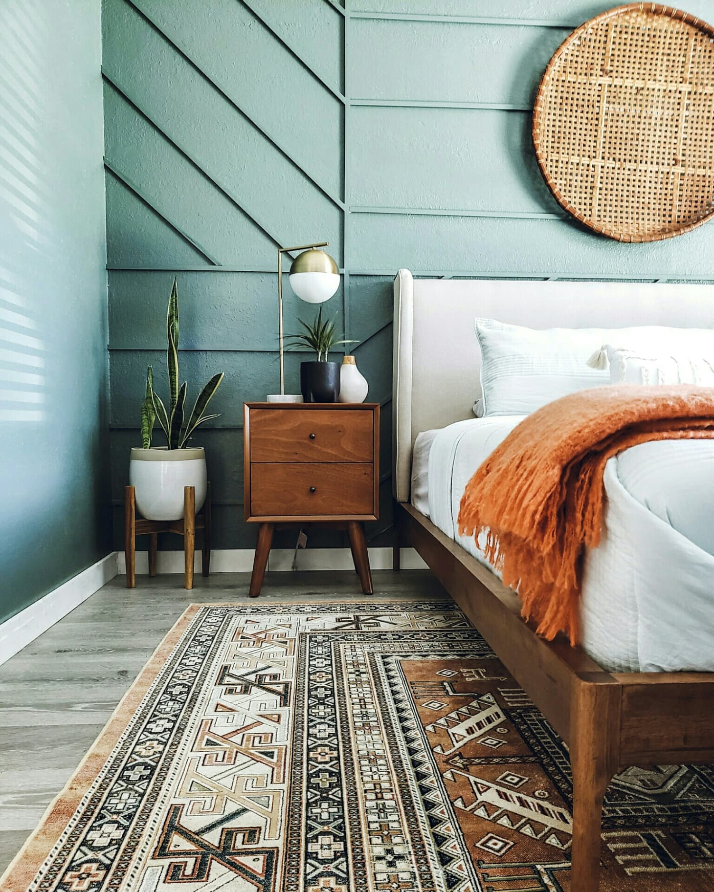 green accent wall with tangerine colored rug and blanket