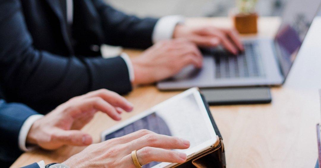 Photo de deux hommes qui utilisent des tablettes et ordinateurs