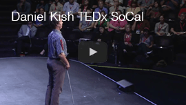 YouTube video thumbnail shows Lead Visioneer Daniel Kish on stage in front of the audience in the background at the 2011 TEDx SOCal event in Long Beach, California.