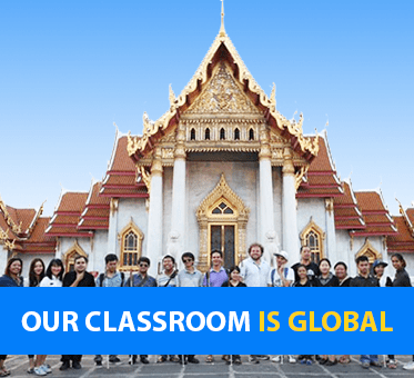Our Classroom Is Global. Photo shows Visioneers Daniel Kish and Brian Bushway standing with blind student coaches in front of a temple in Thailand.