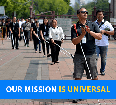 Our Mission Is Universal. Visioneer Juan Ruiz leads a group of blind student coaches in Bangkok.