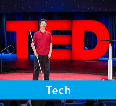 Photo for Tech drop-down banner shows World Access For The Blind President Daniel Kish onstage as a keynote speaker at the global TED conference in Vancouver with the lit TED logo sign behind him. Click the down arrow to expand the text field.