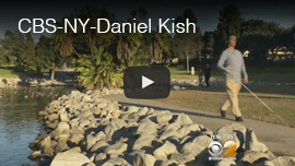 Video image:l Daniel Kish walking next to a pond in a park in Long Beach, California. Caption: video report by CBS New York.