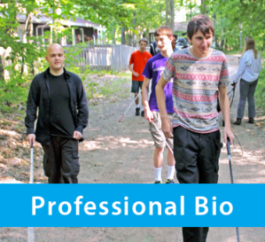 Photo banner box shows J Steele-Louchart walking with blind students along a path at 'The Road Lies Ahead' summer camp in Michigan.