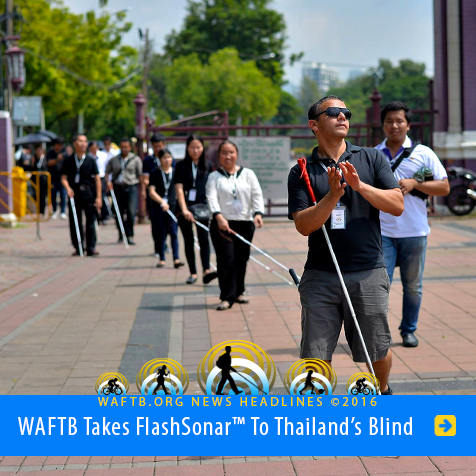 Headline: World Access For The Blind takes Flash Sonar to Thailand's blind. Image: WAFTB Instructor Juan Ruiz claps his hands to gauge the size of a public square as he leads blind coaching students in Bangkok, Thailand.