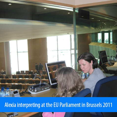 Alexia interpreting at the EU Parliament in Brussels 2011. Image. Photo shows Alexia sitting at the desk in the interpreting booth with the seating area for Members of the European Parliament visible through the glass wall.